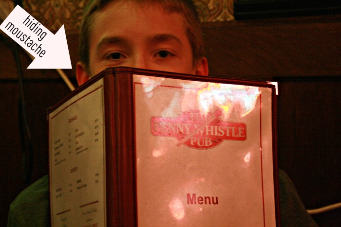 Alex hiding behind Penny Whistle Menu